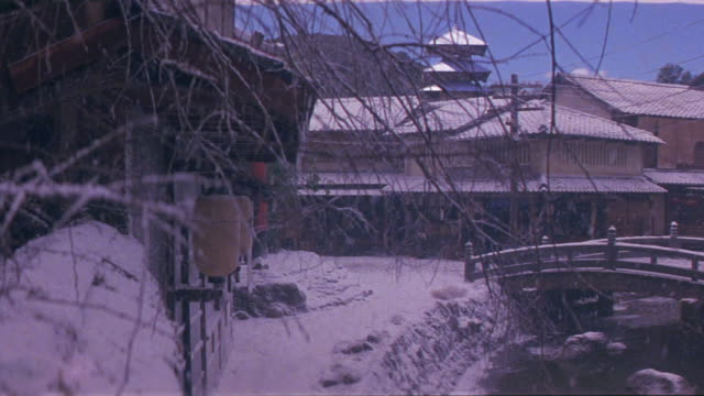 vidéos et rushes de medium angle of japanese town or village. snow is falling and covers ground, arched foot bridge over stream or river, and roofs of multi-story buildings. pagoda in background. wood building in left foreground has paper lanterns hanging by entrance. pedest - bare tree