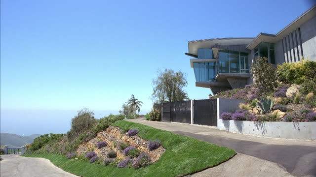vidéos et rushes de medium angle of concrete modern two story house. see square window turret extending from houses. see green and purple bush landscaping. see blue sky in background. see ocean in background. see single lane driveway leading to house. matching dx/nx 2749-001 - malibu