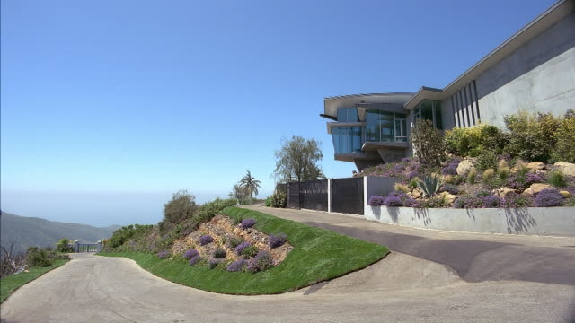 medium angle of concrete modern two story house. see square window turret extending from houses. see green and purple bush landscaping. see blue sky in background. see ocean in background. see single lane driveway leading to house. matching dx/nx 2749-001 - malibu stock videos & royalty-free footage