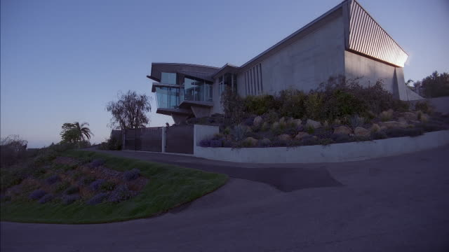 medium angle of concrete modern two story house. see square window turret extending from houses. see green and purple bush landscaping. see blue sky in background. see single lane driveway leading to house. see black metal grate in front of house. see ang - malibu stock videos & royalty-free footage
