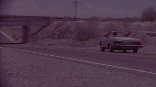 MEDIUM ANGLE OF CREAM-COLORED TWO-DOOR CAR IN MIDDLE OF A U-TURN ON EMPTY STRETCH OF FREEWAY OR HIGHWAY. SEE IT DRIVE DOWN THE ROAD AWAY FROM THE CAMERA BELOW SUNNY SKIES. BRIDGE OR HIGHWAY IS BUILT OVER THE ROAD.