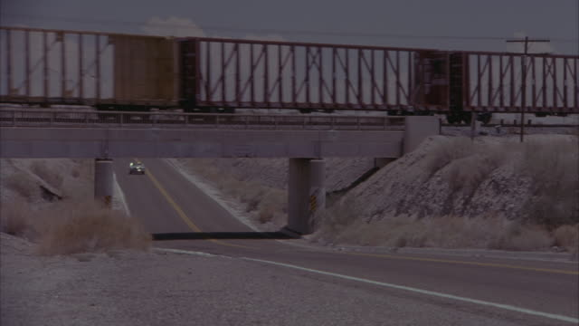 MEDIUM ANGLE OF WHITE BIG-RIG TRUCKS AND PICK-UP TRUCKS. SEE DRIED TREES OR BRUSH IN THE FOREGROUND AS CARS PASS BY. CAMERA SLOWLY PANS LEFT TO SEE CREAM-COLORED TWO-DOOR MERCEDES CONVERTIBLE DRIVING DOWN FREEWAY TOWARD THE CAMERA.