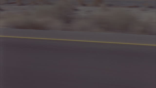 PROCESS PLATE OF DESERT ROAD PASSING BY FROM POINT OF VIEW OF MOVING VEHICLE. CREAM-COLORED TWO-DOOR MERCEDES CONVERTIBLE DRIVES PAST. DRIED BRUSH GROWS IN DESERT SANDS THAT DIVIDE OPPOSING TRAFFIC ON THE FREEWAY.