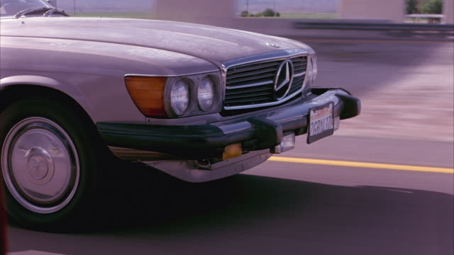 MEDIUM ANGLE OF FRONT OF CREAM-COLORED TWO-DOOR MERCEDES CONVERTIBLE. SEE WHEELS OF CAR SPINNING AS MERCEDES DRIVES DOWN OPEN ROAD OF FREEWAY OR HIGHWAY.