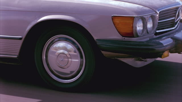MEDIUM ANGLE OF FRONT OF CREAM-COLORED TWO-DOOR MERCEDES CONVERTIBLE. SEE WHEELS OF CAR SPINNING AS MERCEDES DRIVES DOWN OPEN ROAD OF FREEWAY OR HIGHWAY. SEE REFLECTION OF OTHER CARS IN SHINY METAL OF HUB CAP.
