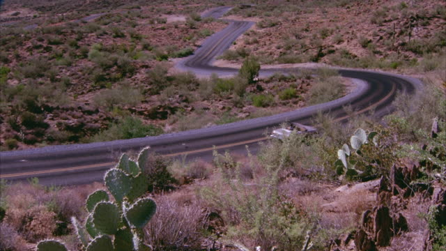 WIDE ANGLE OF ROLLING GREEN HILLS OR SLOPED MOUNTAINS OF DESERT. CAMERA PANS DOWN TO SEE CREAM-COLORED MERCEDES CONVERTIBLE DRIVING DOWN WINDING ROAD OR FREEWAY THAT CUTS THROUGH DESERT, DESERT HIGHWAY. SEE CACTI AND DRIED BRUSH GROWING ON DESERT SANDS.