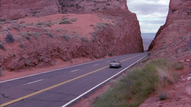 PAN DOWN TO SEE EMPTY STRETCH OF FREEWAY, DESERT HIGHWAY CUTTING THROUGH DESERT MOUNTAINS PASS. SEE CREAM-COLORED MERCEDES CONVERTIBLE DRIVE DOWN ROAD. OVERCAST DAY.