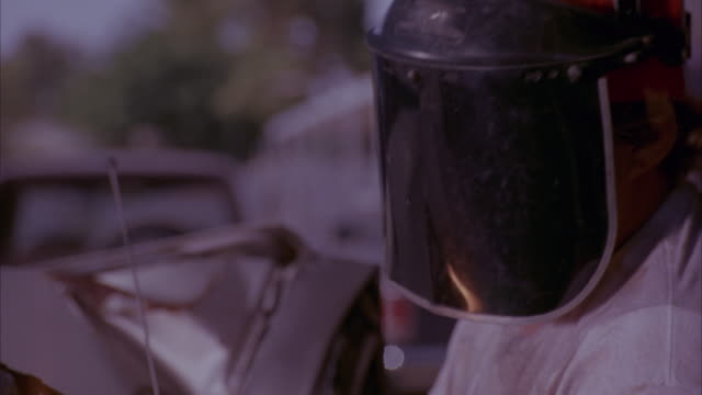medium angle of mechanic holding blowtorch to meld together metal on the top of a severely damaged car. mechanic is wearing white t-shirt, red trucker hat, and black protective mask over face. mechanic looks up toward camera. fire from blowtorch swirls ou - mechanic stock videos & royalty-free footage