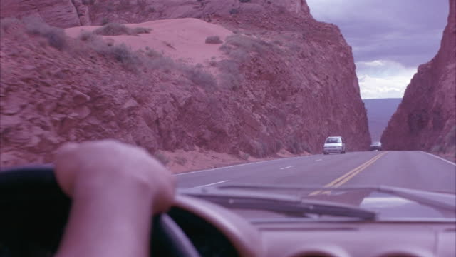 wide angle, driving pov of highway through desert mountain landscape. red rock.  hand of driver in the foreground. mountain road lined with railing along cliff. freeway. dashboard of 1978 mercedes-benz 450 sl. - 1978 stock videos and b-roll footage