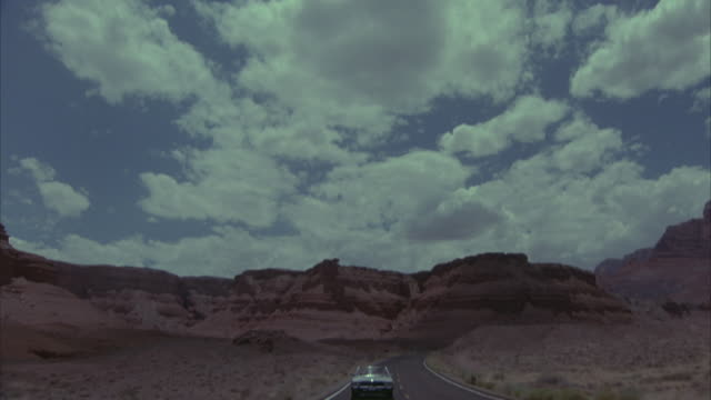 WIDE ANGLE OF CREAM-COLORED MERCEDES CONVERTIBLE DRIVING TOWARD THE CAMERA ON OPEN FREEWAY CURVING THROUGH DESERTS. SEE WHITISH ROCKS ON EITHER SIDE AS CAR DRIVES DOWN ROAD. CAMERA SEEMS TO BE MOUNTED ON CAR. CAMERA PANS UP TO SEE PUFFY WHITE CUMULUS CLOU