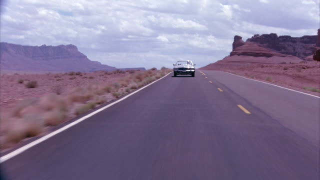 WIDE ANGLE OF CREAM-COLORED MERCEDES CONVERTIBLE DRIVING TOWARD THE CAMERA ON OPEN FREEWAY CURVING THROUGH DESERTS. SEE WHITISH ROCKS ON EITHER SIDE AS CAR DRIVES DOWN ROAD. CAMERA SEEMS TO BE MOUNTED ON CAR.