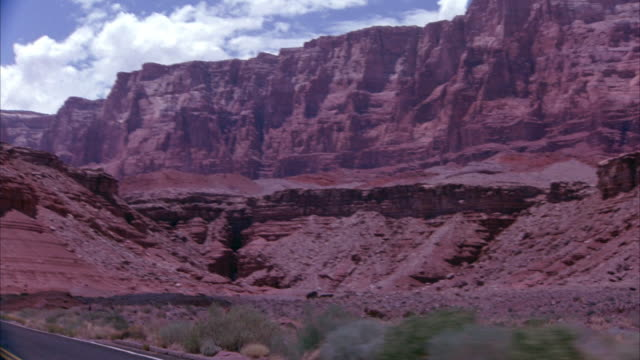 WIDE ANGLE OF CREAM-COLORED MERCEDES CONVERTIBLE DRIVING TOWARD THE CAMERA ON OPEN FREEWAY CURVING THROUGH ROCK FORMATIONS IN DESERTS. CAMERA SEEMS TO BE MOUNTED ON CAR DRIVING IN FRONT OF CONVERTIBLE. SEE DESERT FOLIAGE ON EITHER SIDE OF THE ROAD.