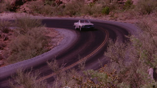 MEDIUM ANGLE OF  WINDING DESERT HIGHWAY. CAMERA PULLS BACK TO SEE CREAM-COLORED MERCEDES DRIVING TOWARD CAMERA. SEE BUSHES AND CACTUS DOTTING BARREN LANDSCAPE. SEE THORNS ON CACTUS.