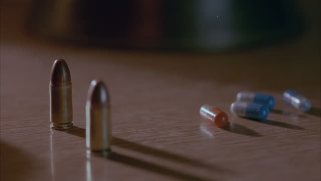 close angle of three golden bullets, three blue and white pills and one red capsule pill or medicine sitting on brown desk. see hand come into frame and pick up each bullet one at a time. shot has shallow depth of field as several bullets are out of focus - {{relatedsearchurl('capsule pipeline')}} stock videos and b-roll footage