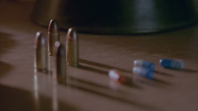 close angle of five golden bullets, three blue and white pills and one red capsule pill or medicine sitting on brown desk. see hand come into frame and pick up each bullet one at a time. shot has shallow depth of field as several bullets are out of focus. - {{relatedsearchurl('capsule pipeline')}} stock videos and b-roll footage