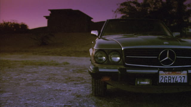 medium angle of 1980's mercedes convertible parked in rural or desert area during dusk. see small, single story brick building on hill in background. see green trees in background. - cabrio stock-videos und b-roll-filmmaterial