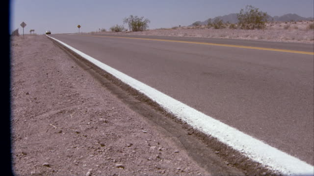 wide angle of 1978 mercedes-benz 450 sl convertible driving on desert highway toward camera. desert landscape. cars. - mercedes benz stock videos and b-roll footage