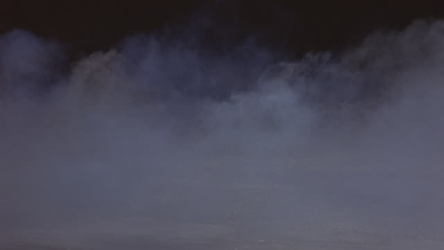 MEDIUM ANGLE OF WHITE CLOUDS OF FOG ROLLING ACROSS GROUND AT NIGHT. SEE BLACK SKY IN THE BACKGROUND AS THICK FOG BLOWS SLOWLY FROM LEFT TO RIGHT.