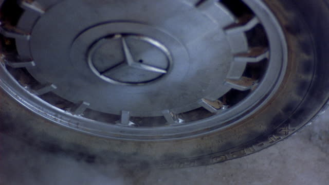 close angle of tire with shiny mercedes benz logo. rubber of tire is coated in dust. see reflection of debris in the hubcap. tire spins until white smoke rises from it. - mercedes benz stock videos & royalty-free footage
