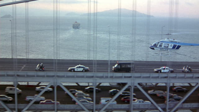 aerial of police convoy on bay bridge. see black van flanked by two  police cruisers and four policemen on motorcycles.  helicopter flies next to convoy. traffic on lower section driving in opposite direction. camera follows convoy as it exits yerba buena - coit tower stock videos & royalty-free footage