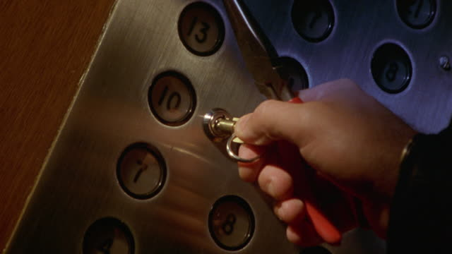 CLOSE ANGLE OF ELEVATOR PANEL INDICATING FLOOR NUMBERS. MAN'S HAND PUTS KEY INTO KEYHOLE. MAN THEN GRIPS KEY WITH NEEDLENOSE PLIERS AND TURNS KEY CLOCKWISE. NUMBER TEN BUTTON LIGHTS UP. HAND TAKES KEY OUT OF KEYHOLE.