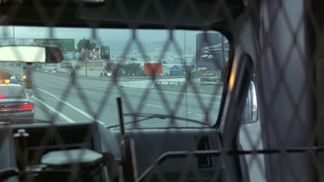 process plate driving in police motorcade exiting bay bridge. see police car with flashing lights and police on motorcycles through metal grate and front window of police bus. prisoner pov. could be prisoner transport vehicle or van. shaky camera. bizbars - 囚人点の映像素材/bロール