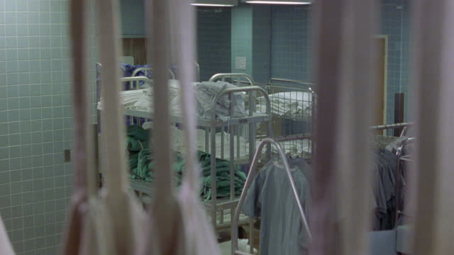 stockvideo's en b-roll-footage met wide angle of hospital laundry room. pov behind curtains. see piles of scrubs on metal shelves. room has tile walls. could be mental institution facility. shirts on rack. clothing. - operatiekleding