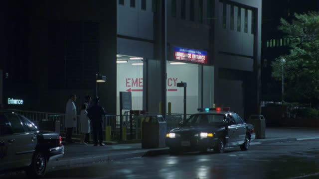 "wide angle of hospital exterior. see motorcycle drive into hospital's ""ambulance entrance"". nurse and doctor in lab coats talk to an officer near entrance. police cars with sfpd insignia are parked on street with lights flashing. location is actually pitt - nordkalifornien bildbanksvideor och videomaterial från bakom kulisserna"