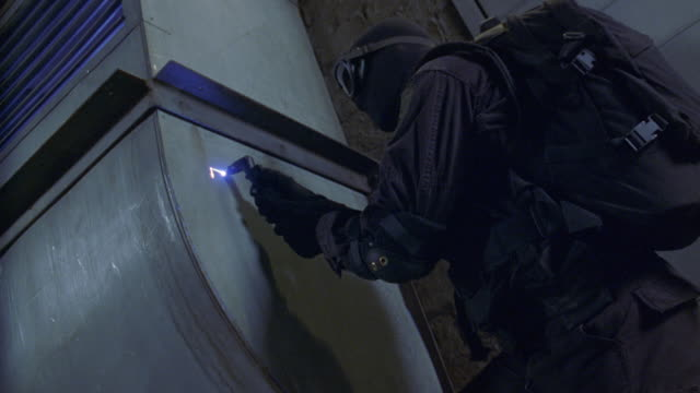 medium angle of man in black clothes, backpack, and a mask breaking into a storage room or metal vent. man uses high powered or laser torch to cut the thin metal wall. man peels back metal and climbs in. could be thief, robber, or criminal. - 黒のシャツ点の映像素材/bロール