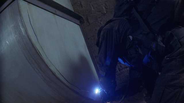 vídeos y material grabado en eventos de stock de medium angle of man in black clothes, backpack, and a mask breaking into a storage room or metal vent. man uses high powered or laser torch to cut the thin metal wall. man peels back metal and climbs in. could be thief, robber, or criminal. - robo