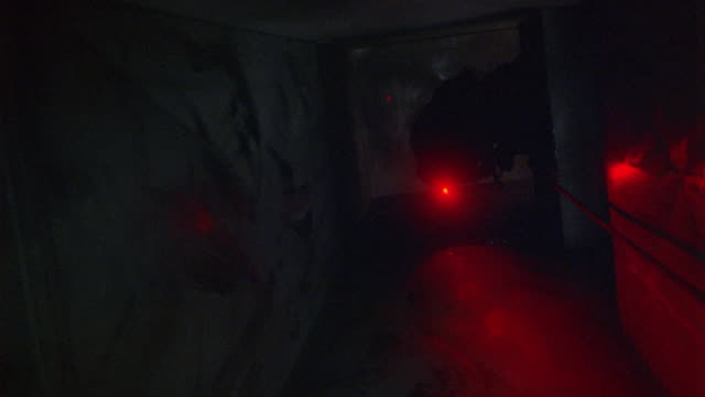 medium angle of air duct, shaft or large vent in a building. see black rope dangling along left side of shaft. thief or robber in black clothes and a mask with red light on his head descends down rope head first. criminal spins feet first before getting t - air duct stock videos & royalty-free footage