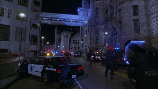 medium angle of crime scene. see multiple police cars and police officers in position. see police member in foreground aiming large searchlight up against glass bridge on top frame. see bridge connecting two multi-story stone buildings. see street lamps a - searchlight stock videos and b-roll footage