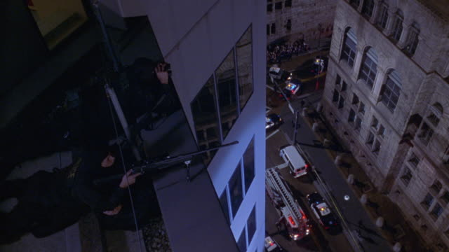 HIGH ANGLE DOWN ON SWAT TEAM MEMBERS LYING IN POSITION WITH MACHINE GUNS POINTING FROM HIGH RISE BUILDING BALCONY. SEE CITY STREET WITH SPECTATORS AND POLICE CARS WITH FLASHING LIGHTS ON RIGHT. SEE TWO MULTI-STORY HIGH RISE BUILDINGS, COULD BE DOWNTOWNS.
