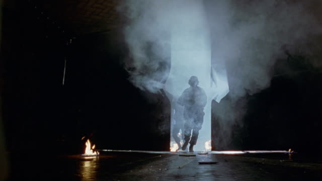 medium angle of empty warehouse or garage with small fire flames or pits throughout. see large hole through warehouse door or garage door in foreground. see light beaming through broken hole of door. see swat team open doors and run in with search lights - 1998 stock-videos und b-roll-filmmaterial