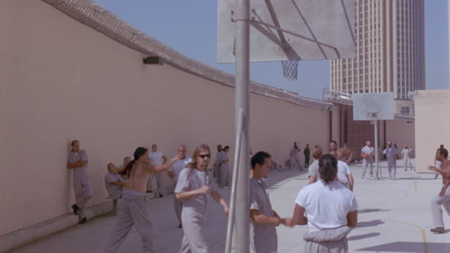 MEDIUM ANGLE OF JAIL MATES, PRISONERS PLAYING BASKETBALL IN COURT. SEE MULTIPLE MEN IN GRAY JUMPSUITS SITTING ON BENCHES, PLAYING BASKETBALL, SMOKING CIGARETTES, AND WALKING IN FOREGROUND.