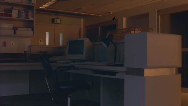 MEDIUM ANGLE OF OFFICE OR MEDICAL OFFICE. SEE DESK WITH CHAIR IN FOREGROUND. SEE FLASHING LIGHTS THROUGH DOUBLE DOORS IN BACKGROUND. COULD BE USED FOR HORROR, ACTION,  OR THRILLER SCENES. SHAKY CAMERA.