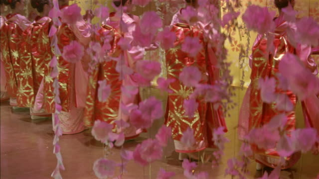 vidéos et rushes de high angle down of geishas wearing kimonos, dancing on stage. shot begins with japanese paper lanterns in foreground, then pans down to see women dancing with fans. dancers move between long strings of cherry blossom flowers hanging from ceiling. - geisha