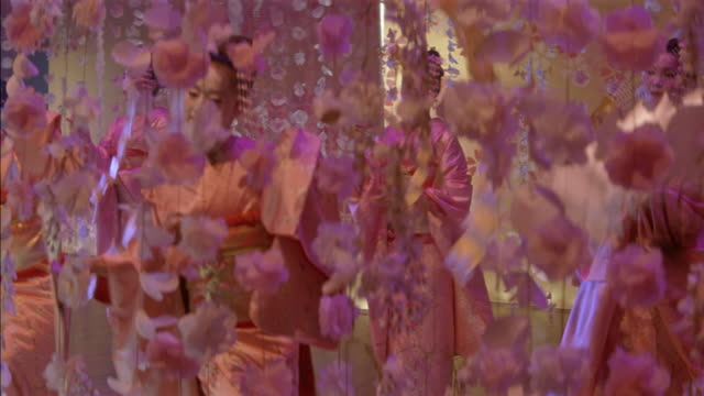 vidéos et rushes de high angle down of geishas wearing kimonos, dancing on stage. shot begins with japanese paper lanterns in foreground, then pans down to see women dancing with fans. dancers move between long strings of cherry blossom flowers hanging from ceiling. - japon