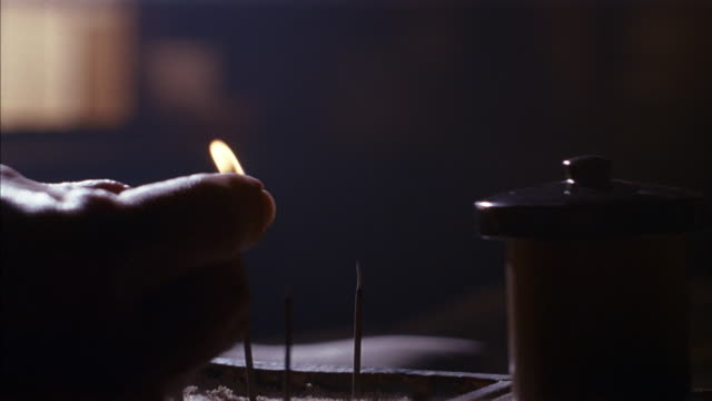 vídeos de stock e filmes b-roll de close angle of man's hand lighting match in dark room. hand brings lit match to a new stick of incense standing upright in an incense holder next to older incense sticks. as incense stick is lit, flame is blown out, causing incense to begin smoking. camer - incenso