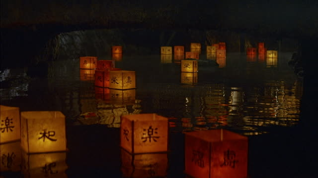 medium angle of red and yellow paper lanterns floating down stream or river under bridge. square lanterns have chinese characters written on them. camera cranes up to reveal men and women walking across bridge. men wearing suits and hats or kimonos. women - lantern stock videos & royalty-free footage
