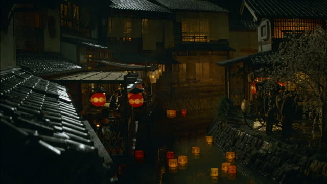 HIGH ANGLE DOWN OF JAPANESE TOWN. MULTI-STORY TILE ROOF BUILDINGS ON BOTH SIDES OF FRAME, STREAM OR SMALL RIVER RUNS DOWN CENTER OF FRAME. RED AND YELLOW PAPER LANTERNS FLOAT DOWN STREAM. BUILDINGS ON LEFT HAVE COVERED DECKS WHERE PEOPLE ARE DINING OR HAV