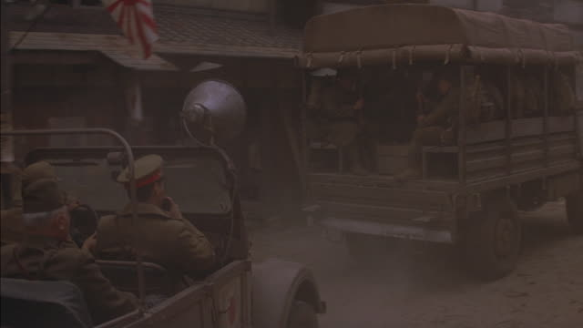 high angle down of street in japanese town or city. shot starts with close angle of military vehicle tires moving across frame from left to right. camera rises up to reveal truck full of military personnel, followed by army jeep. men in uniforms ride in j - convoy trucks stock videos and b-roll footage