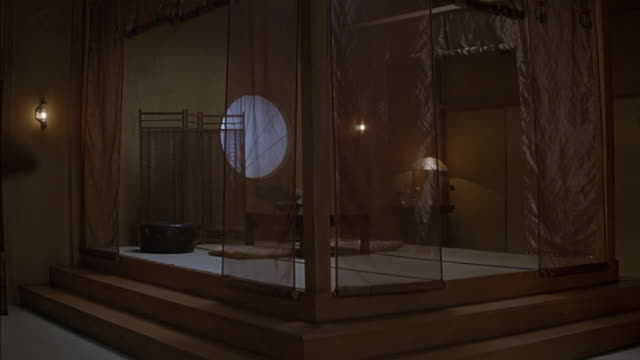 medium angle of raised platform in japanese style room. three steps lead to platform and sheer curtains hang around it. a small table sits in center with two cushions resting on bamboo mat floor. steaming pot or container, could be food. large circular wi - screen partition stock videos and b-roll footage
