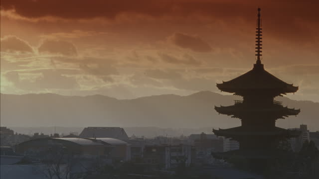 wide angle of japanese town or city. multi-story pagoda on right side amid many houses and other buildings. could be temple or shrine. mountains in background and sun is shining through clouds in sky. - pagoda点の映像素材/bロール
