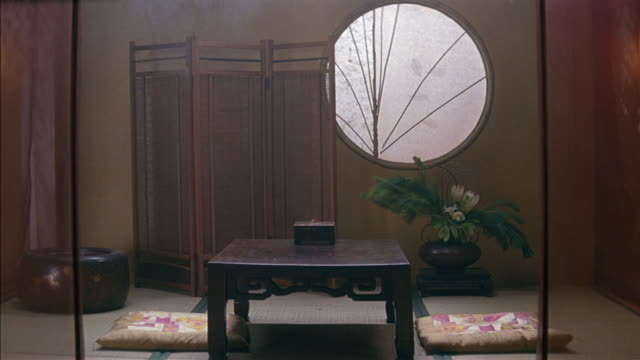 medium angle of japanese style dining room. sheer curtains hang in front of table and two cushions resting on bamboo mat floor. steaming pot or container, could be food. large circular window on back wall, folding screen or partition and potted plant on b - screen partition stock videos and b-roll footage