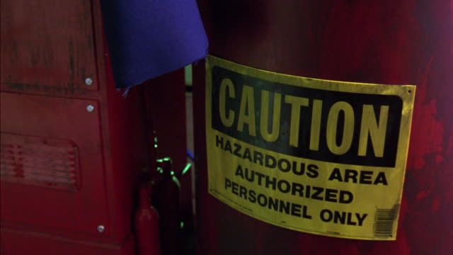 "close angle of sign in auto shop or mechanic's garage reading ""caution hazardous area authorized personnel only"". sign is posted on red barrel next to metal cabinet or tool box. neg. cut. blue rag hanging in frame is pulled off screen. - hazardous area sign stock videos & royalty-free footage"