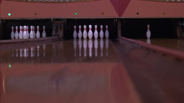 vídeos de stock, filmes e b-roll de medium angle of three lanes in bowling alley from low pov. bowling ball is rolled down center lane towards pins. ball hits one pin on far right side. pin spotter comes down and picks up remaining pins, sweeps lane, then sets them back down. sports. - cancha de jogo de boliche