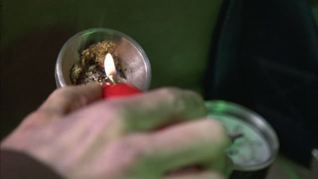 CLOSE ANGLE OF MARIJUANA IN PIPE OR BONG. MAN'S HAND LIGHTS POT WITH RED LIGHTER. NEEDLE ON AIR PRESSURE GAUGE IN BACKGROUND FLUCTUATES AS POT IS SMOKED. DRUGS, DRUG USE. NEG. CUT.