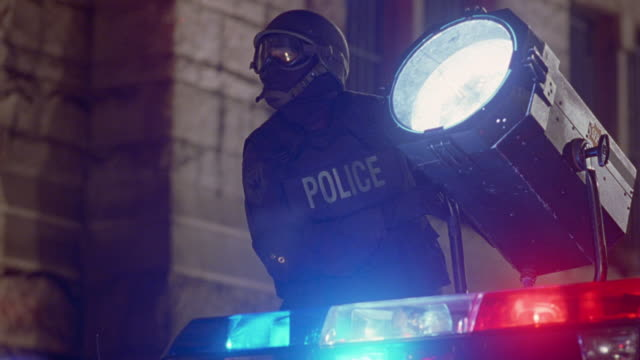 wide angle of police officer shining search light. could be swat team member wearing helmet, goggles, face mask, and bullet-proof vest at police stand-off. see flashing lights from bizbar below with stone building in background. sparks fly as glass light - fly swat stock videos & royalty-free footage