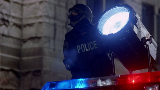 wide angle of police officer shining search light. could be swat team member wearing helmet, goggles, face mask, and bullet-proof vest at police stand-off. see flashing lights from bizbar below with stone building in background. see sparks fly as glass li - fly swat stock videos & royalty-free footage